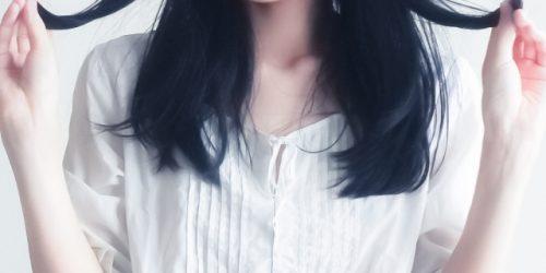 髪の毛先をつまむ女性